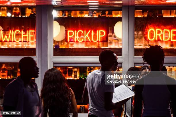 TOPSHOT People stand queue to order food for pick up on a deserted Ocean drive in Miami on March 18 2020 They crowded beaches and crammed nightclubs...
