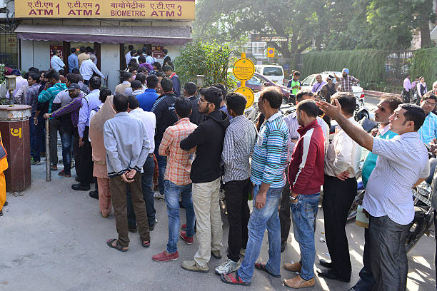People stand to withdraw currency outside a Punjab National Bank ATM in New Delhi