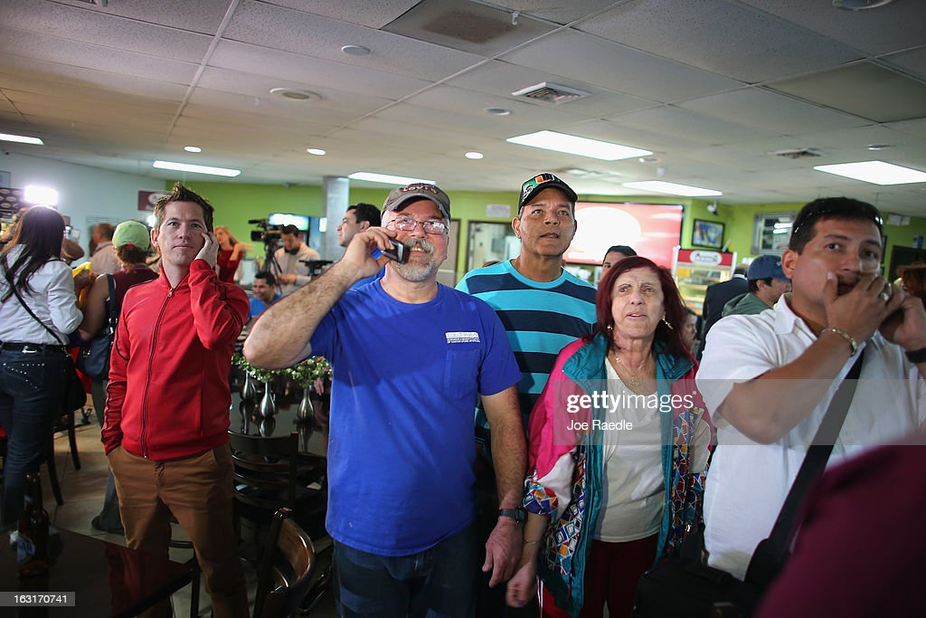 People stand together as they listen to television sets reporting on the death of Venezuelan president Hugo Chavez, at El Arepazo 2 a restaurant in the heart of a neighborhood that has the largest concentration of Venezuelans in the U.S. on March 5, 2013 in Doral, Florida. The Venezuelan government announced today that Hugo Chavez lost his battle with cancer.