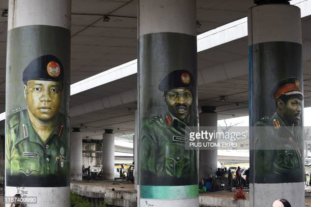 People stand under the bridge at Obalende in Lagos on July 23 2019 by pillars with street art portraits of President Mohammadu Buhari flanked by...