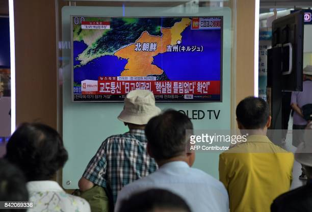 People stand watching a television display at a train station in Seoul on September 3, 2017 showing a news broadcast about North Korea's latest...