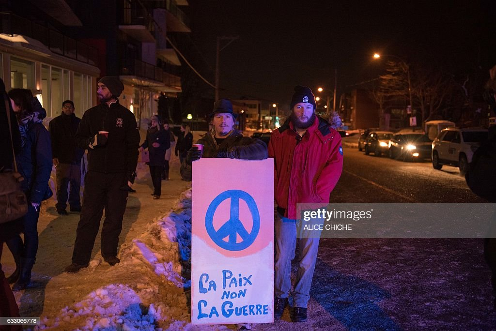 People stand with a peaceful sign near the Québec City Islamic cultural center after a shooting occurred in the mosque on Sainte-Foy Street in Quebec city on January 29, 2017. Two arrests have been made after five people were reportedly shot dead in an attack on a mosque in Québec City, Canada. / AFP / Alice Chiche