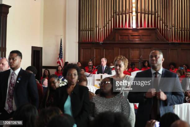 People stand with their backs to Democratic presidential candidate former New York City mayor Mike Bloomberg as he speaks during a worship event at...