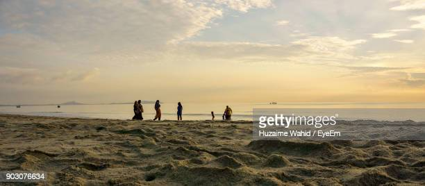 People Standing Against Sea During Sunset
