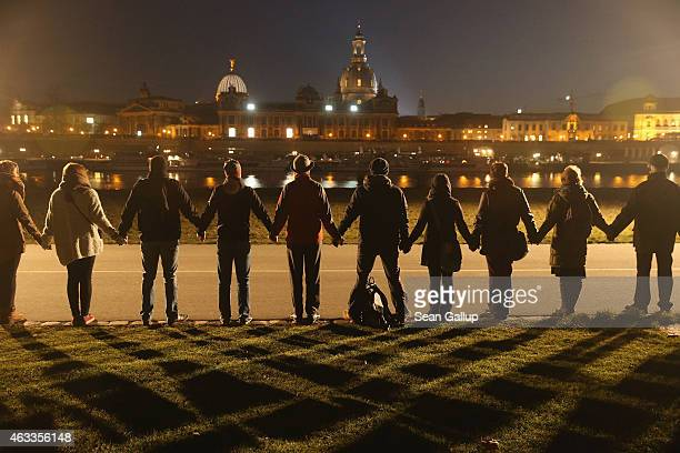 People standing along the Elbe River across from the Dresden city center link hands to create a human chain in commemoration of the 70th anniversary...