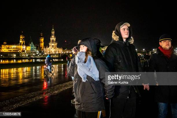 People standing along the Elbe River across from the historic Dresden city center link hands to create a human chain in commemoration of the 75th...