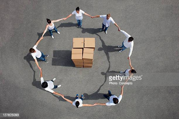 pessoas em pé ao redor empilhadas caixas - grupo médio de pessoas - fotografias e filmes do acervo