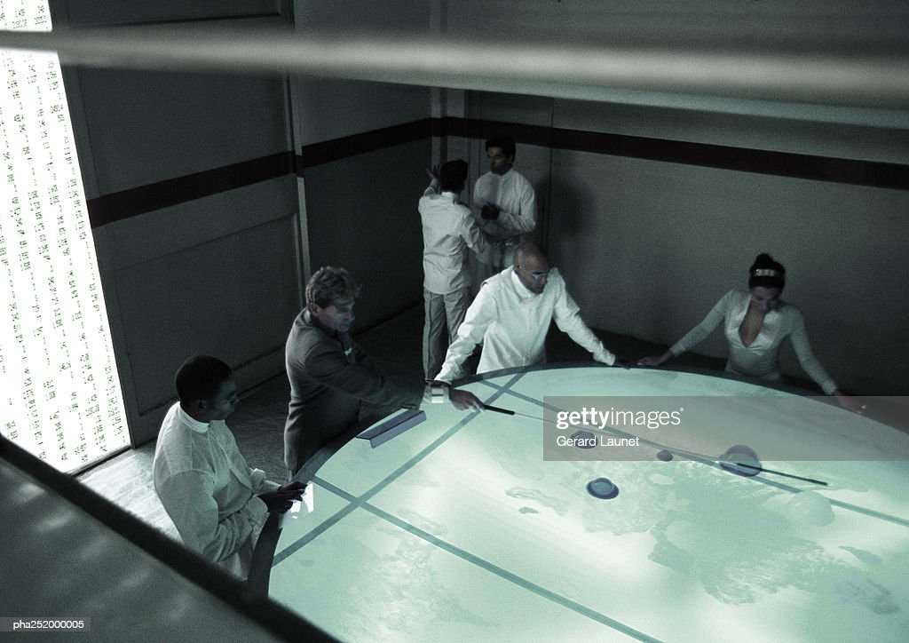 People standing around table, high angle view : Stockfoto