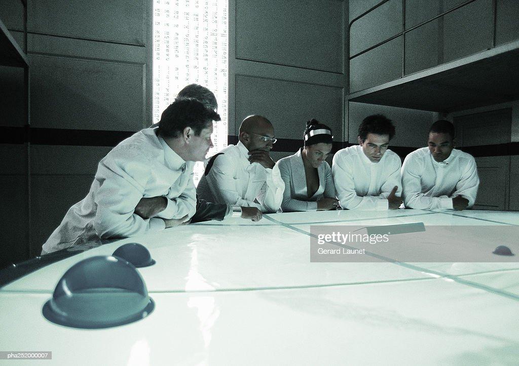 People standing around table : Stockfoto