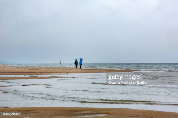 People Standing At Beach Against Sky