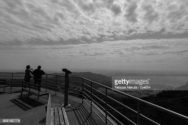 People Standing At Observation Point Looking At View