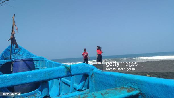 People Standing By Boat At Beach