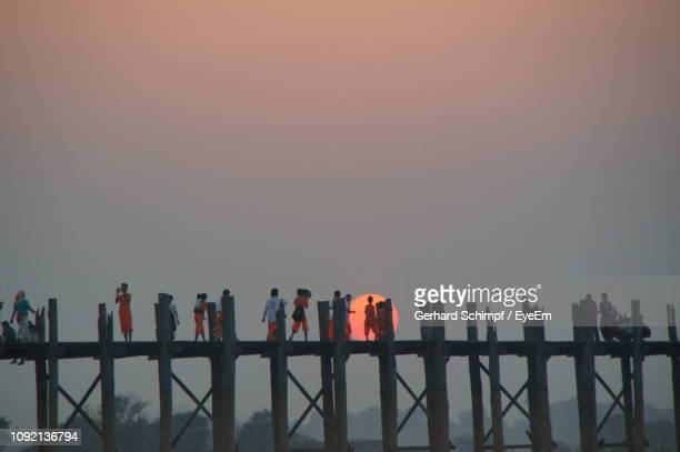 people standing by bridge during sunset - gerhard schimpf stock pictures, royalty-free photos & images