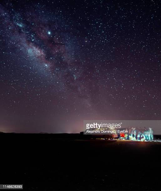people standing by cars on field against sky at night - jeddah stock pictures, royalty-free photos & images