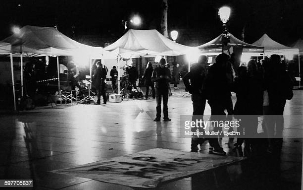 people standing by rip paris sign on illuminated floor at night - rest in peace stock photos and pictures