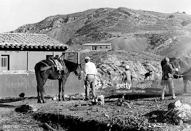 People standing by some farmhouses in the Contrada Lannari in the Agrigento district during the area regeneration sponsored by the Ente di...