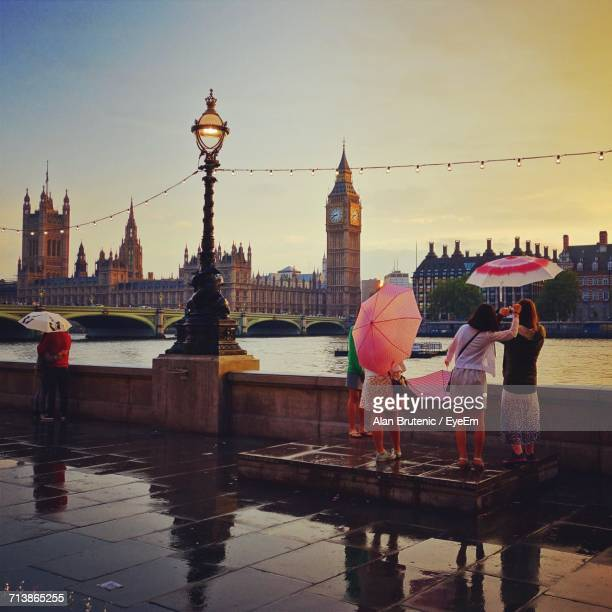 People Standing By Thames River Looking At Big Ben In City During Rainy Season