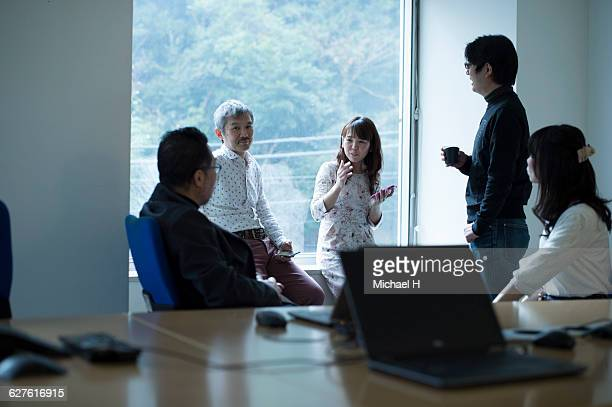 people standing by windows of conference room