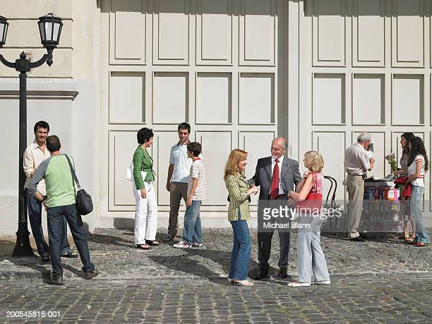 People standing in busy street talking to each other