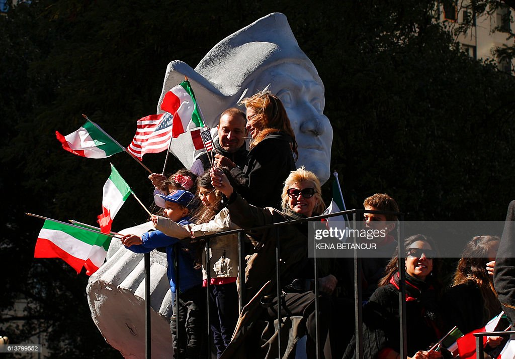 People standing in front of a statue of Christopher Colombus wave the Italian and American flags during the annual Columbus Day parade in New York on October 10, 2016. Columbus Day is a national holiday in many countries in the Americas and elsewhere which officially celebrates the anniversary of Christopher Columbus' arrival in the Americas on October 12, 1492. Many Italian-Americans observe Columbus Day as a celebration of their heritage, the first occasion being in New York City on October 12, 1866. / AFP / KENA