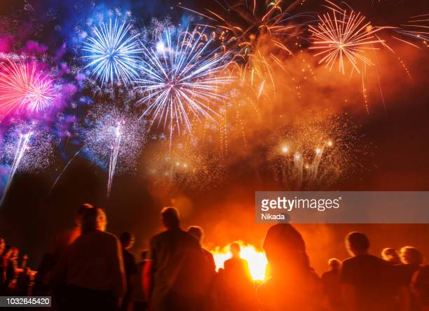 people standing in front of colorful firework - new year's eve stock pictures, royalty-free photos & images