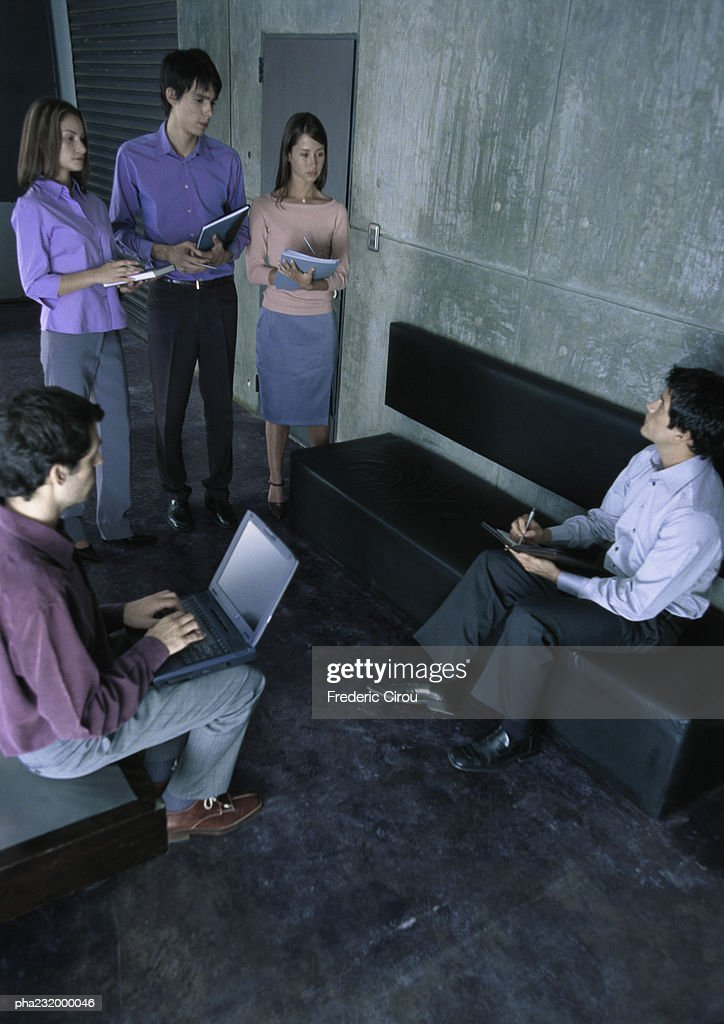 People standing in group looking at man writing, man on laptop. : Stockfoto