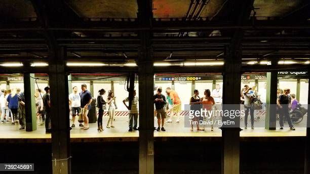 people standing in illuminated corridor - new york city subway stock pictures, royalty-free photos & images