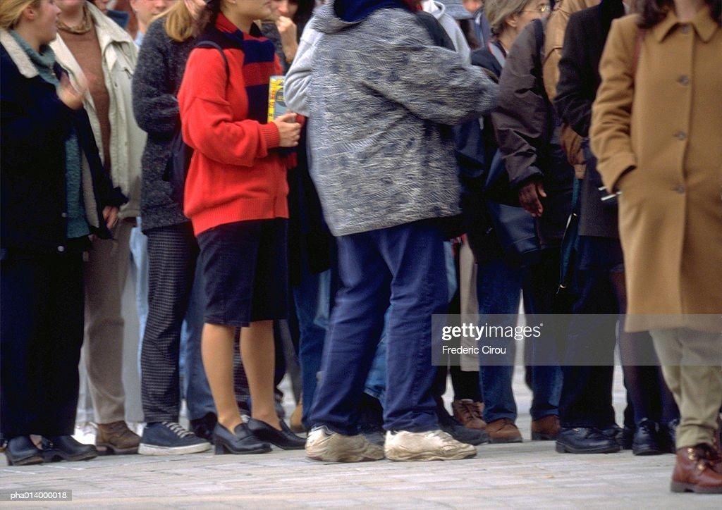 People standing in line on sidewalk, neck down : Stockfoto