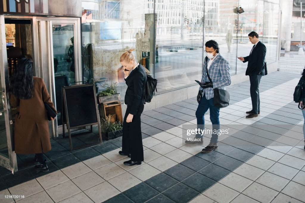 People standing in line outside cafe keeping distance : Stock Photo