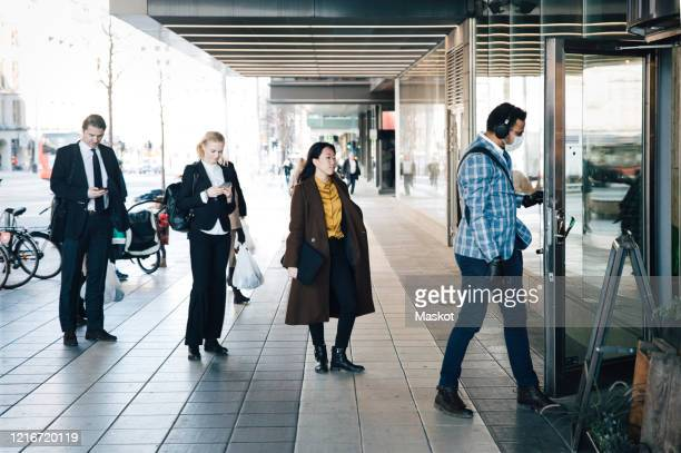 people standing in line outside cafe - social distancing stock pictures, royalty-free photos & images