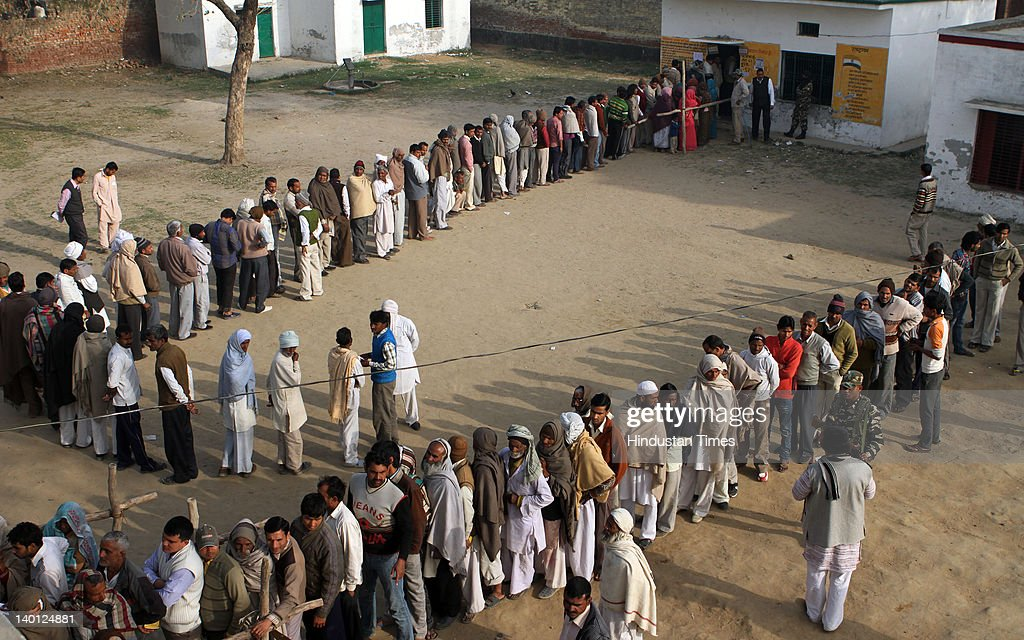 People standing in queue at polling booth in Bhatta village of Jevar assembly constituency as near International circuit during sixth phase of assembly elections in Uttar Pradesh February 28, 2012 in Gautambudh Nagar, India. The twin villages of Bhatta- Parasual become centre of the land acquisition row last summer after the police opened fire at protesting villagers killing two.