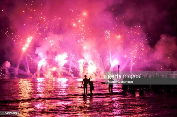People standing in sea illuminated by fireworks, Abruzzo, Italy
