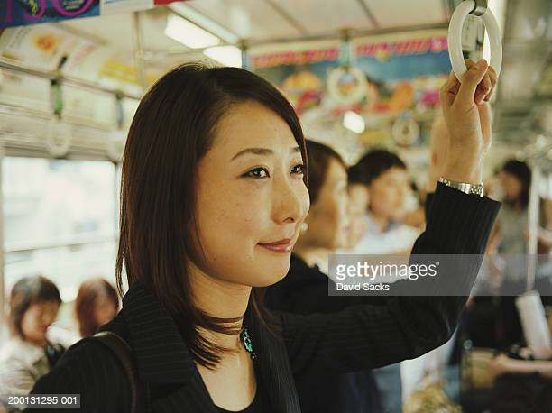 People standing in subway car (focus on businesswoman)