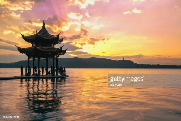 People standing in the pavilion and watching the sunset,Hangzhou,China