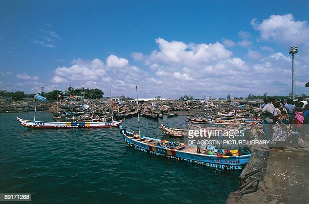 People standing near a fishing boat, Lome, Togo