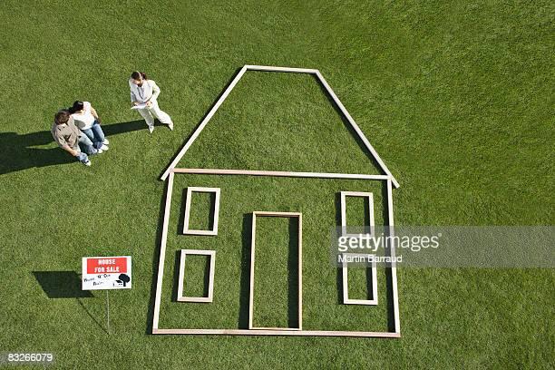 Personnes debout près du symbole maison parce sale'et de contour