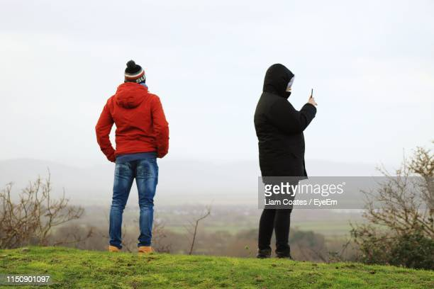 people standing on grassy field against sky during foggy weather - rear view stock pictures, royalty-free photos & images