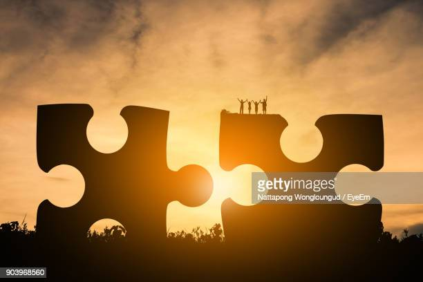 People Standing On Large Jigsaw Pieces Against Sky During Sunset