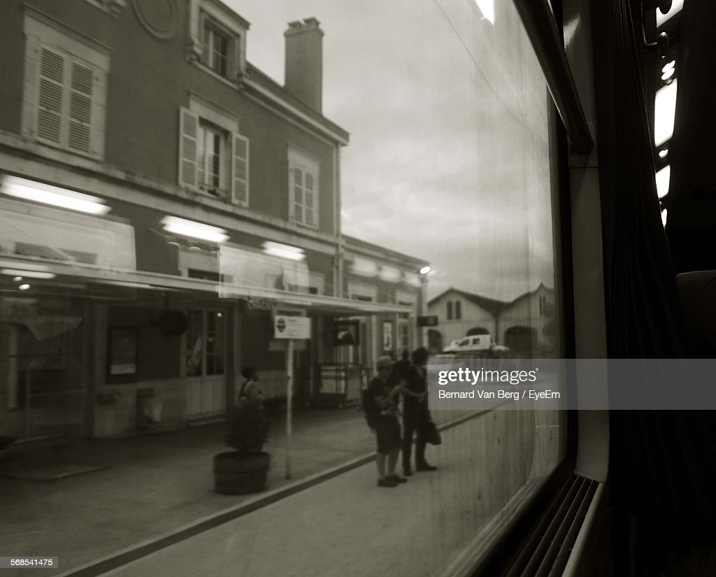 People Standing On Railroad Station Platform Seen From Train Window : Stock Photo