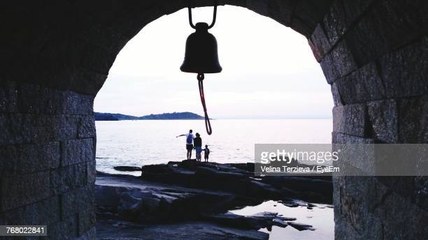people standing on rock against sea - bell stock pictures, royalty-free photos & images