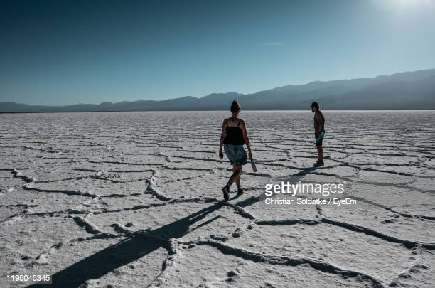 people standing on salt flat - christian soldatke stock pictures, royalty-free photos & images