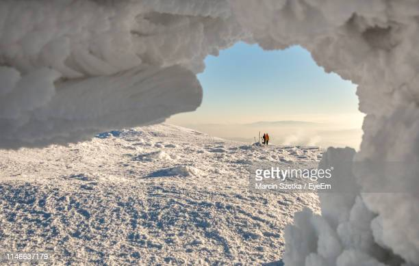 people standing on snow covered mountain against sky - babia góra mountain stock pictures, royalty-free photos & images