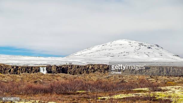 People Standing On The Edge Of Almannagja Fault And Oxarafoss Waterfall, Thingvellir National Park, Iceland