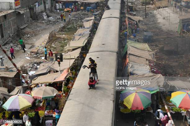 People standing on top of a running train in Dhaka.