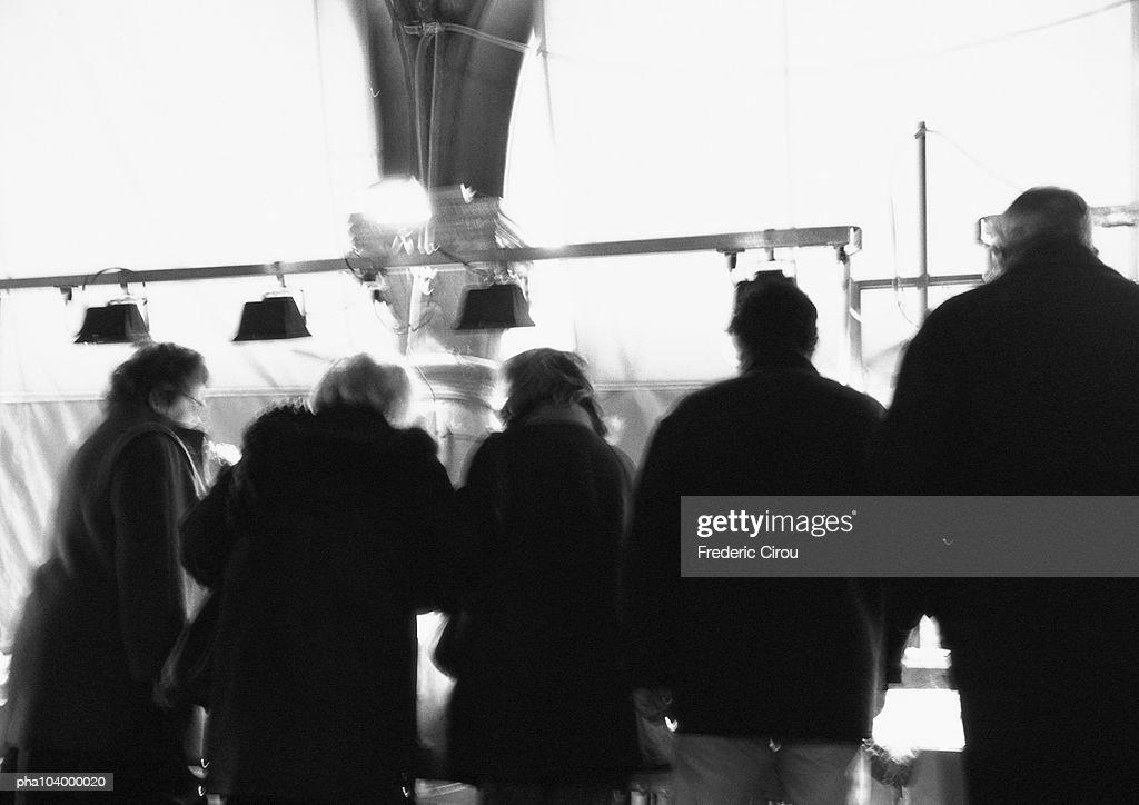 People standing side by side, rear view, b&w : Stockfoto