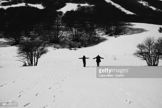 People Standing With Arms Outstretched On Snow Covered Landscape