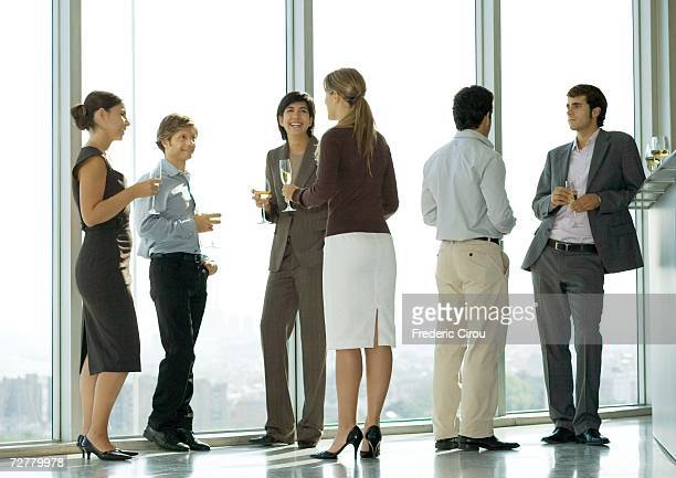 people standing with glasses during office party - cocktail party stock pictures, royalty-free photos & images