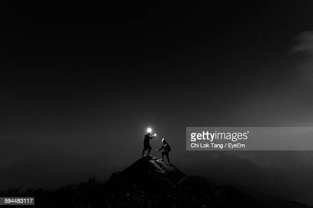 people standing with illuminated lighting equipment on rock at night - conquering adversity stock pictures, royalty-free photos & images
