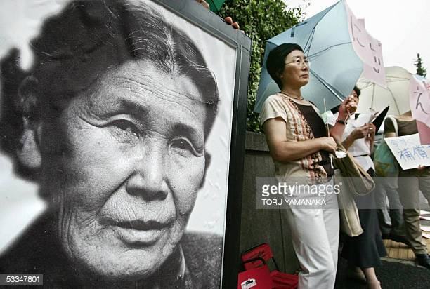People stands beside a portrait of late comfort woman Kim HakSun of South Korea during a demonstration in front of the national parliament in Tokyo...