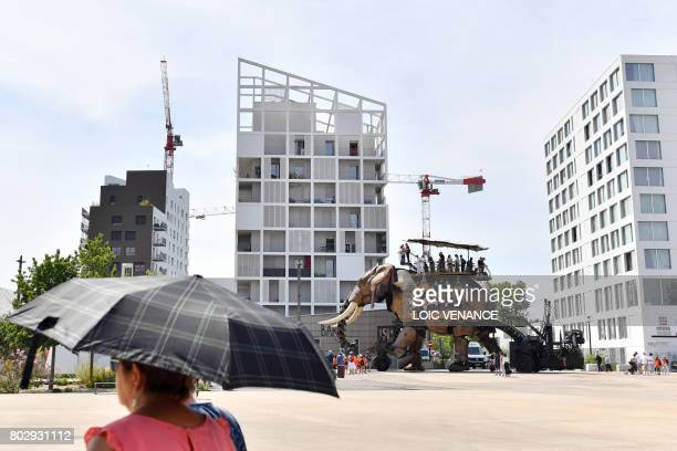 People stands on a mechanical elephant made of wood and steel at 'Les Machines de L'Ile' in Nantes western France on June 20 2017 as people look at...